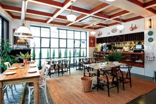 테이블 사이를 넓히고 유리벽을 설치해 널찍하고 시원한 느낌이 드는 내부 인테리어.