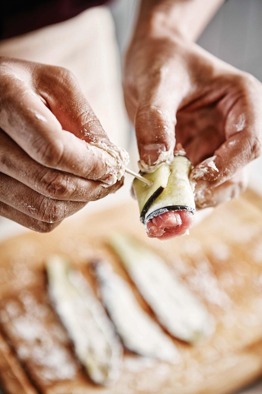 가지탕수육을 만들기 위해 가지에 돼지고기를 넣어 돌돌 만 뒤 이쑤시개로 고정시키는 모습.