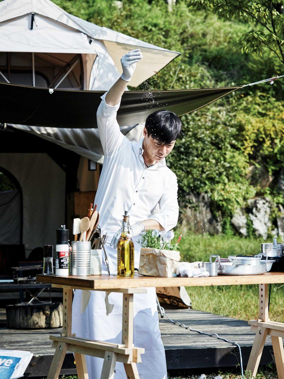 1 ——— 최현석 셰프가 그의 전매 특허인 소금 뿌리기 포즈로 글램핑 요리를 시연 중이다.