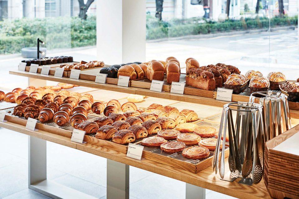 크로와상, 까눌레, 식빵 등 갓 구운 빵들이 먹음직스럽게 진열대에 놓여 있다.