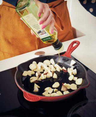 감바스 알 아히요를 만들기 위해 팬에 마늘과 새송이버섯, 페페론치노를 넣고 올리브유를 둘러 볶고 있다.