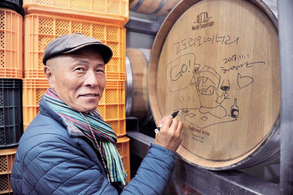 고도리 와이너리 와인 숙성 통에 사인과 즉흥적인 그림을 남기고 있는 허영만 화백.