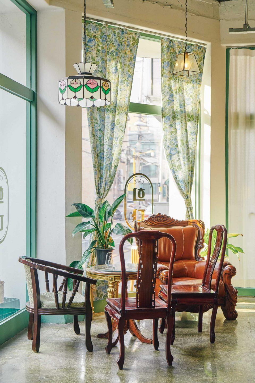 통유리창, 고풍스러운 테이블과 의자, 꽃무늬 커튼이 어우러져 뉴트로 느낌을 강화한다.