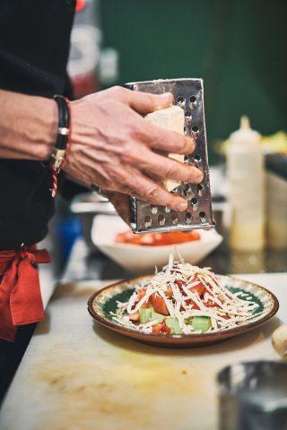 불가리아 전통 요리 샵스카 샐러드에 치즈를 올리고 있는 셰프의 손.