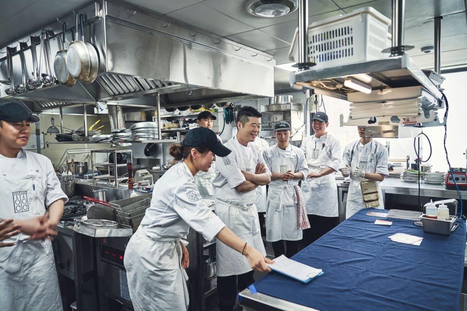 서비스 전 김대천 셰프와 톡톡 요리사들이 한데 모여 오늘의 메뉴와 중요한 사항들을 공유하고 있다.