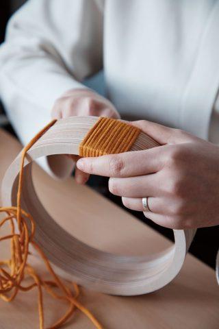 링 형태로 가공한 합판에 한 가닥 한 가닥 실을 감는다.